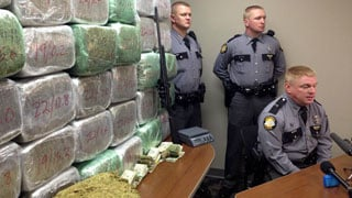 Kentucky State Police show off 900 pounds of marijuana found in a Spencer County home during a press conference
