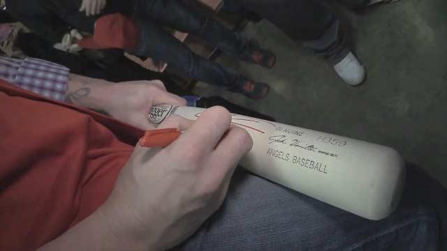 Josh Hamilton signs autographs on Louisville Slugger bats.