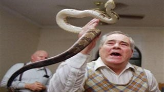 (AP Photo/John Bazemore). FILE - In this Feb. 25, 1995 file photo, Junior McCormick tests his faith by handling a rattlesnake as Homer Browing looks on during services at the Church of the Lord Jesus in Kingston, Ga.