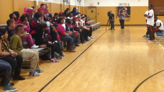 U of L football players encourage teens at the center to stay on the right track and avoid violence.