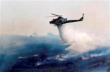(AP Photo). A helicopter attacks a wildfire burning in the north county of San Diego Tuesday, May 13, 2014, in San Diego.