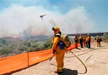 (AP Photo). Firefighters watch from a ridge as a helicopter drops retardant on a out-of- control wild fire Tuesday, May 13, 2014, in San Diego.