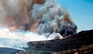 (AP Photo). Billowing smoke rises from flames as firefighters begin the trek up the hills to battle a wild fire, Tuesday, May 13, 2014, in San Diego.