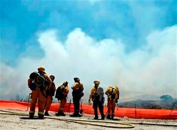 (AP Photo). Firefighters face a huge smoke cloud as they plan their attack on a wild fire Tuesday, May 13, 2014, in San Diego.