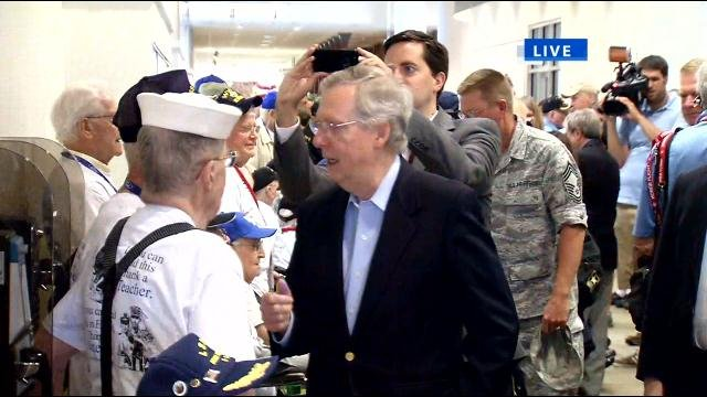 Veterans shake hands with Senator Mitch McConnell before departing Louisville International Airport to visit National World War II Memorial in Washington on the 70th anniversary of D-Day.