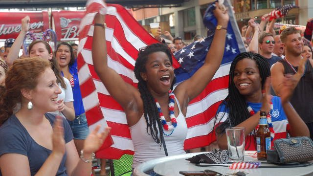 Soccer fans cheer after The Star Bangled banner is played at Fourth Street Live