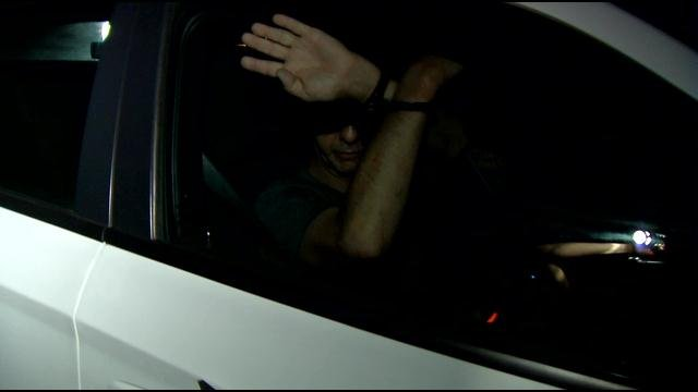 Brooks Elbert hid his face as he was taken away in a police cruiser on June 25.