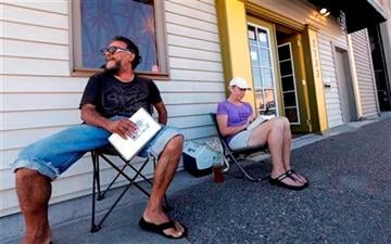 (AP Photo/Elaine Thompson). George Vargas, left, takes a seat next to first-in-line customer Deb Greene in front of the recreational marijuana store Cannabis City Monday, July 7, 2014, in Seattle.