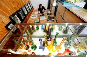 (AP Photo/Ted S. Warren). Krystal Klacsan prepares artwork to be hung, Monday, July 7, 2014 behind a case displaying glass bongs at the recreational marijuana store Cannabis City in Seattle.
