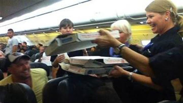 (AP Photo/Logan Marie Torres). In this photo taken Monday, July 7, 2014, a Frontier Airlines flight attendant passes out pizza to passengers aboard a Denver-bound flight diverted to Cheyenne, Wyo.