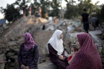 (AP Photo/Khalil Hamra). Palestinian family members sit on the rubble of their destroyed house following an Israeli missile strike late Tuesday, in the town of Beit Hanoun, northern Gaza Strip, Wednesday, July 9, 2014.
