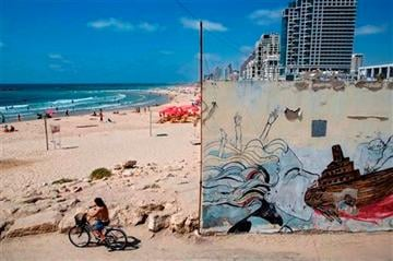 (AP Photo/Oded Balilty). A man rides his bicycle at the Mediterranean Sea beach front, which is normally crowded at this time of year, in Tel Aviv, Israel, Wednesday, July 9, 2014.
