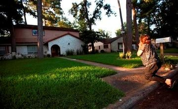 (AP Photo/Houston Chronicle, Cody Duty). Patti Beller prays Thursday, July 10, 2014, in Spring, Texas, outside the home that was the scene of a multiple shooting the night before.