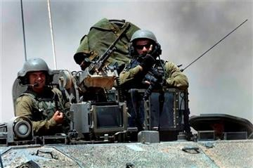(AP Photo/Tsafrir Abayov). Israeli reserve soldiers are seen on the top of an armored personnel carrier returning to Israel from Gaza Strip, southern Israel, Monday, Aug. 4, 2014.