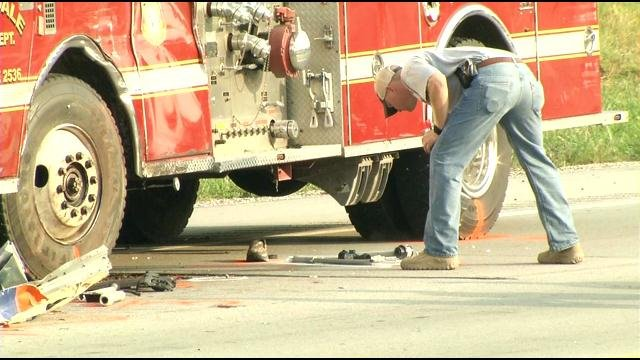 A firefighter cleans up gear on the side of the road after the accident that killed Jonathan French.