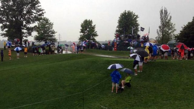 Dedicated fans waiting at the 10th tee while play is suspended.