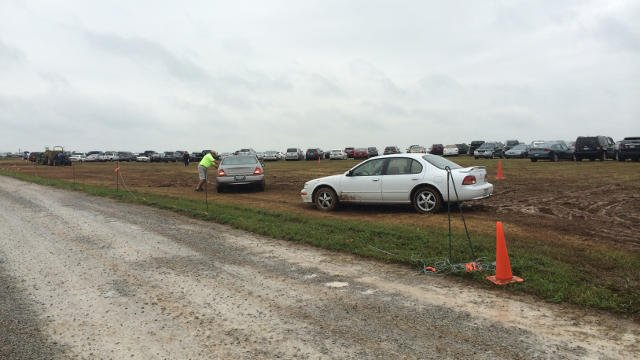 Lot security workers struggle to get cars out of the muddy volunteer lot Friday afternoon.