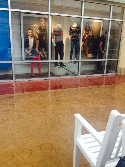 Store employees mop up water leaking into the store.