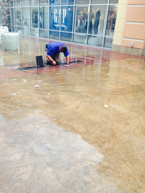 A mall employee works looks at an in-ground drain.