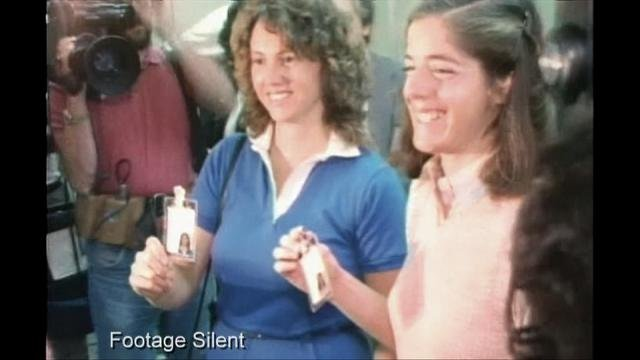 Teacher in Space Christa McAuliffe and backup Teacher in Space Barbara Morgan show reporters their NASA credentials in 1985. (Source: NASA archives, via Spacecraft Films)