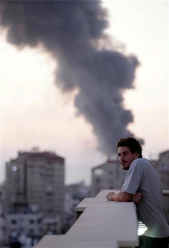 (AP Photo/Lefteris Pitarakis). This photo taken in August, 2014 shows Associated Press video journalist Simone Camilli on a balcony overlooking smoke from Israeli Strikes in Gaza City.
