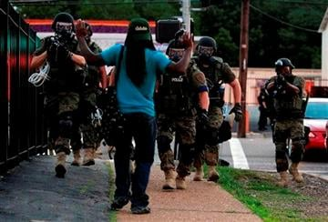 (AP Photo/Jeff Roberson). Police wearing riot gear walk toward a man with his hands raised Monday, Aug. 11, 2014, in Ferguson, Mo.