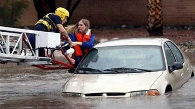Tucson Fire Department personnel use a ladder truck to rescue a woman from a car stranded in rising flood waters in east Tucson, Ariz., Tuesday, Aug. 19, 2014
