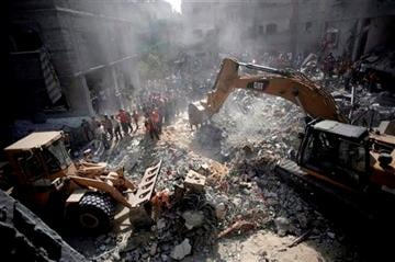 (AP Photo/Khalil Hamra). Palestinians gather around the rubble of a destroyed house following Israeli strikes in the Rafah refugee camp, Southern Gaza Strip, Thursday, Aug. 21, 2014.