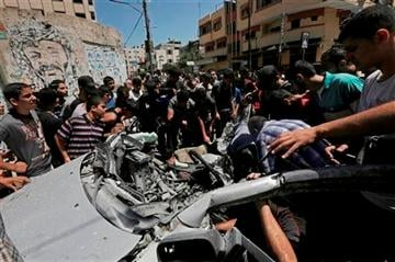 (AP Photo/Adel Hana). Palestinians inspect the wreckage of a vehicle following an Israeli airstrike at the main street in Gaza City in the northern Gaza Strip, Thursday, Aug. 21, 2014.