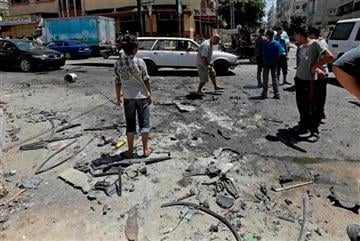 (AP Photo/Adel Hana). Palestinians search the site of the wreckage of a vehicle following an Israeli airstrike at the main street in Gaza City in the northern Gaza Strip, Thursday, Aug. 21, 2014.