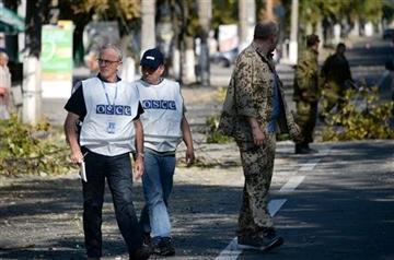 (AP Photo/Mstislav Chernov). Members of the OSCE examine the scene of a shelling in the town of Donetsk, eastern Ukraine, Wednesday, Aug. 27, 2014.