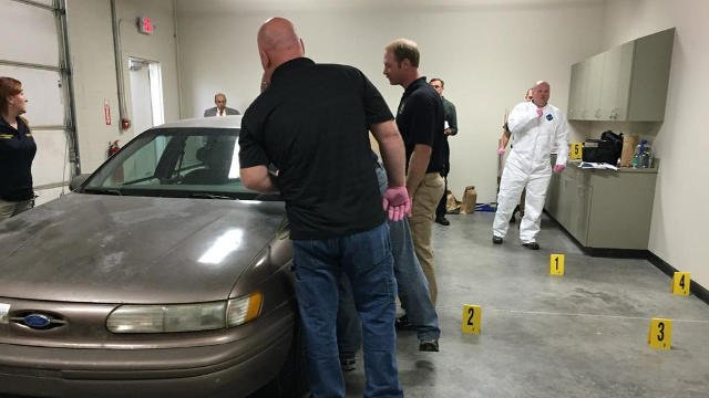 Participants survey the recreation of a crime scene to learn to evaluate a gunshot wound.