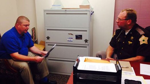 Jamey Noel (right) speaks with a deputy in the office.