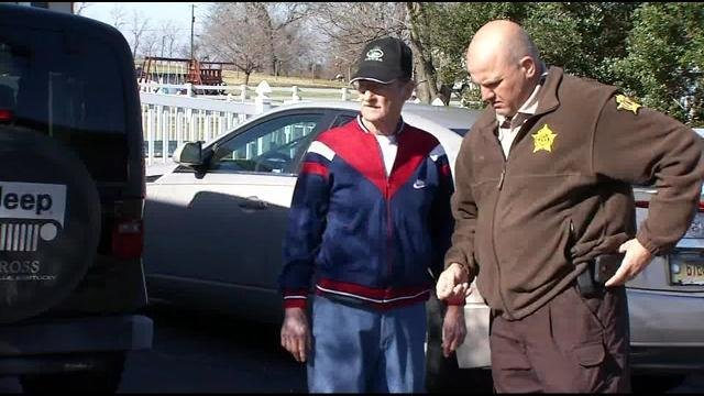 A sheriff's deputy explains the investigation to Hatfield outside his residence.
