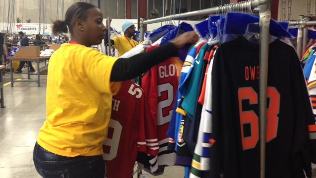 A seasonal worker adds a finished jersey to the rack, where it will undergo quality checks