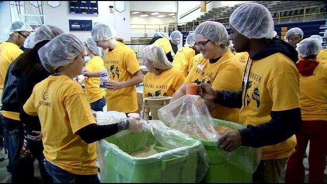 Students work to pack meals in the gymnasium of The Academy @ Shawnee.
