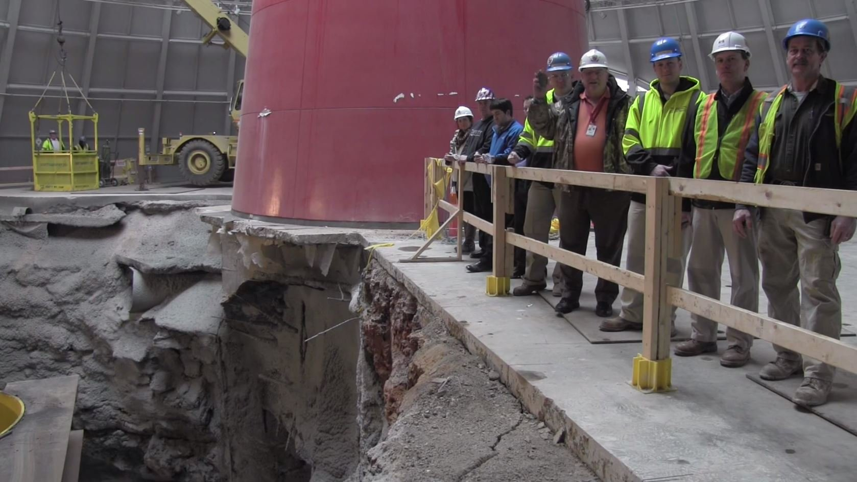 Museum Executive Director Wendell Strode poses with the first rock along with workers who will help to fill the hole. (Courtesy: Corvette Museum/YouTube)