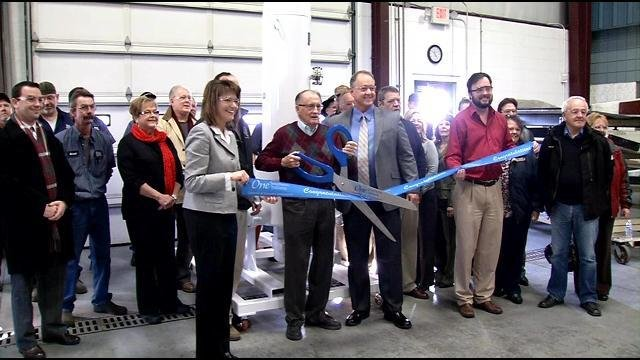 The owner of Spencer Machine and Tools cuts the ribbon on the new expansion.