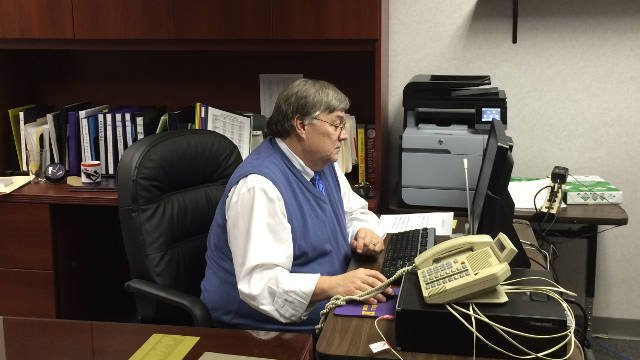 Jim Jury takes a seat at his desk where he will take over as principal of Male High School.