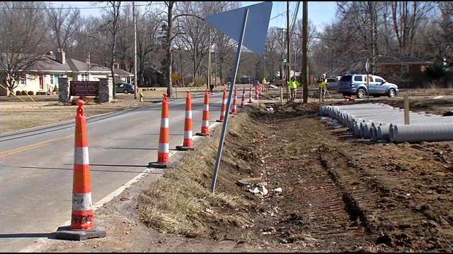 Without sidewalks, people walk on Mount Holly Road every day as cars zoom by them.