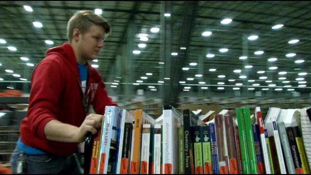 Chegg employee re-shelving books, December 2014 (WDRB)