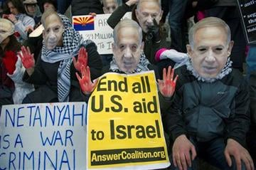 """(AP Photo/Cliff Owen). Pro-Palestine demonstrators wearing Israeli Prime Minister Benjamin Netanyahu masks and symbolic """"blood stained hands,"""" led by Code Pink, protest in front of the Washington Convention Center."""