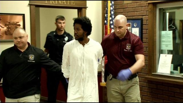 Ronshai Jenefor is escorted out of the Jeffersontown Police Department to be taken to Metro Corrections.