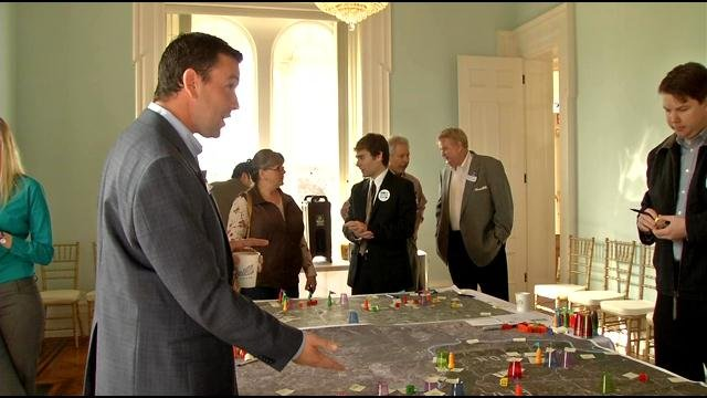 Using plastic cups and post-it notes, one big map of Southern Indiana is used as a drawing board for development.