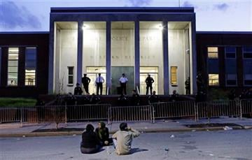 (AP Photo/Patrick Semansky). Protesters sit outside the Baltimore Police Department's Western District police station at the end of a march for Freddie Gray