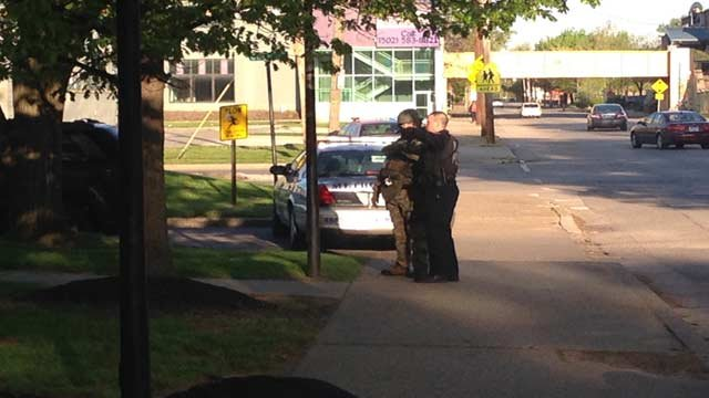 Police officers stand watch outside City View apartments in Louisville after a suspect barricaded himself inside.