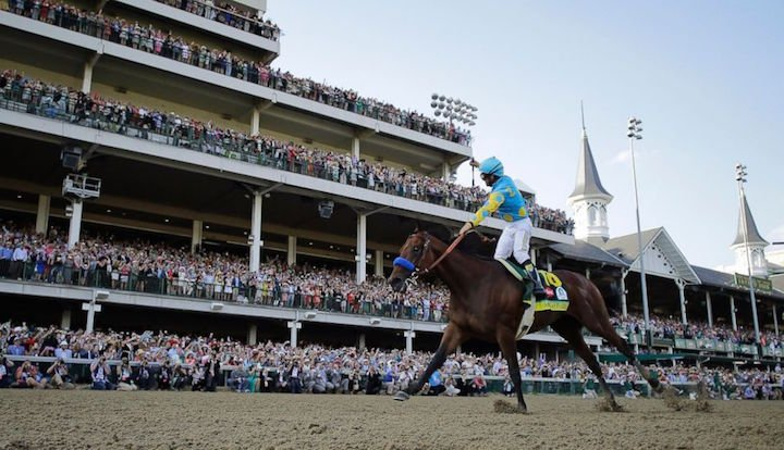 American Pharoah jockey Victor Espinoza waves to the record crowd after winning the Kentucky Derby. (AP photo)