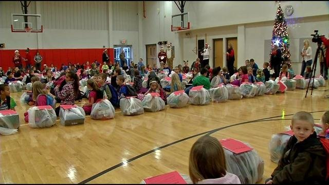 Heth-Washington Elementary students prepare to open their gifts in the gym.