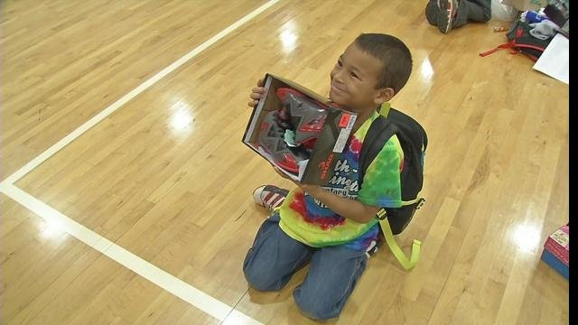 A Heth-Washington student excitedly holds up a new pair of shoes that were purchased with the help of principal Nissa Ellett.