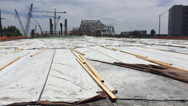The first layer of concrete for the deck of the new downtown bridge sits covered May 12, 2015.